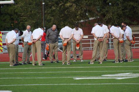 Coaches gather before the start of the Oct. 2 varsity football game at Memorial Stadium against JJ Pearce. Coaches, players, fans, and spirit groups were glad to celebrate Senior night, a Wolverine victory, and to have a season at all. Photo by Mackenzy Klinge.